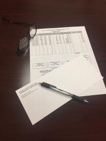 PHoto of BCEC electric bill, glasses, pen and envelope representing bill payment